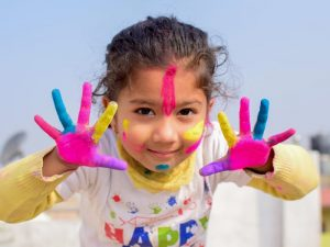 Girl with paint on face and hands