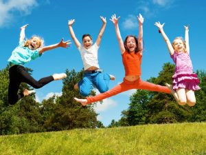 Four kids jumping in field